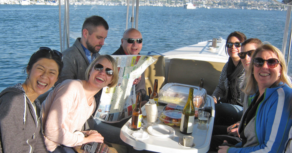 Happy boaters engaging in team offsite fun in Newport Harbor